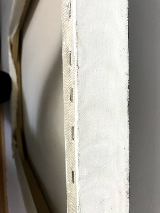 This stapled canvas was stretched across a wooden frame and primed with gesso. Conservators have discussed the merits of staples versus nails.