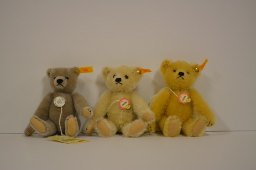 Three stuffed bears sit next to each other.
