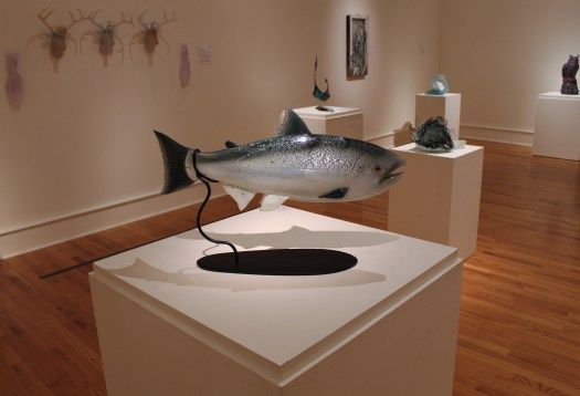 A realistic, glass sculpture of a fish. Attached to its base by a single wire, it appears the fish is swimming in the air.