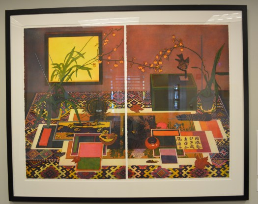 A diptych is one work consisting of two pieces. In this diptych, you can see the line between the two halves. The work is an indoor scene, atop a table are multiple postcards, a box, a birds nest with eggs, and flowers. Against the wall is a mirror, reflecting one of the plants.