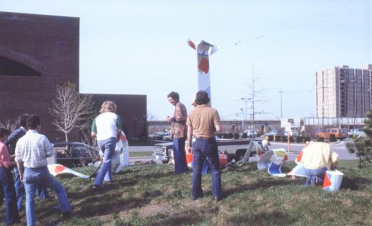"The artist with volunteers installing ""Gambol Series No. 1"" in front of the Community Center for the Performing Arts (now the Arts United Center), April, 1979. The 43-foot long sculpture was borrowed from its home location on Roosevelt Island, New York for the event in Fort Wayne."
