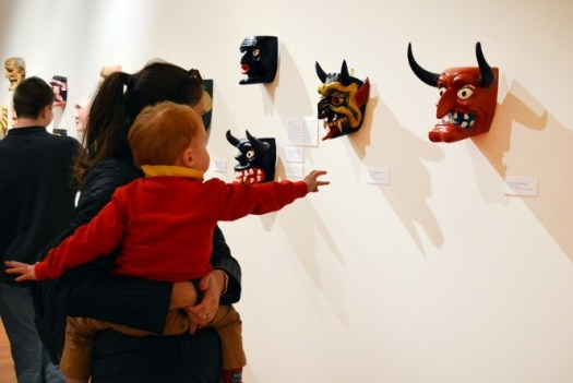 A mother with her young son looks at the Mexican masks on display at the museum. The child reaches out towards a devilish red mask with horns and a grimacing smile.