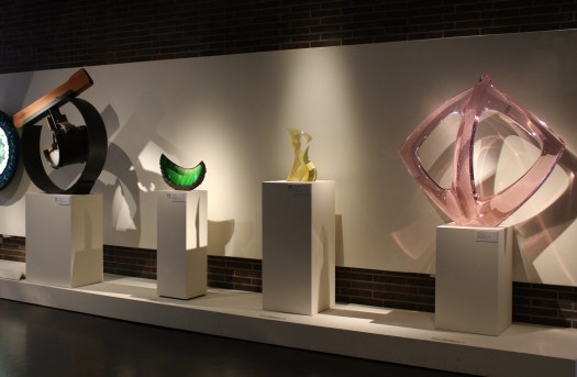 This image features multiple glass pieces in the art museums contemporary glass collection. Each piece is individually lit, to ensure that it sparkles and shines the way the artist wanted.