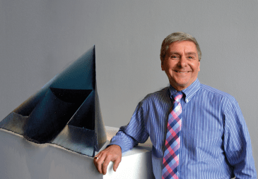A photo of FWMoA President & CEO Charles Shepard standing next to a work of studio glass.