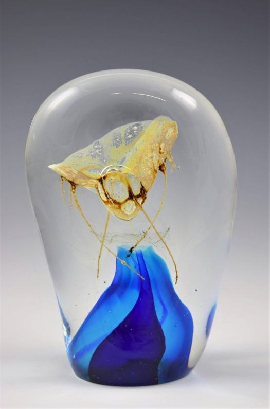 This glass piece is clear except at the bottom, where a blue wave extends into the center. At the very center rests a bug, sort of like a fly, in gold and brown. The sculpture looks like the artist captured a fly in glass.