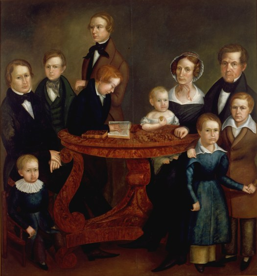 A painted portrait of the Hanna Family, they are gathered around a large oak table. The father and mother are seated on the right-hand side, the mother with a baby in her lap. The seven other children are dispersed around the table, with one son sitting at the table and reading. All of the children are different ages, and all of them are boys.