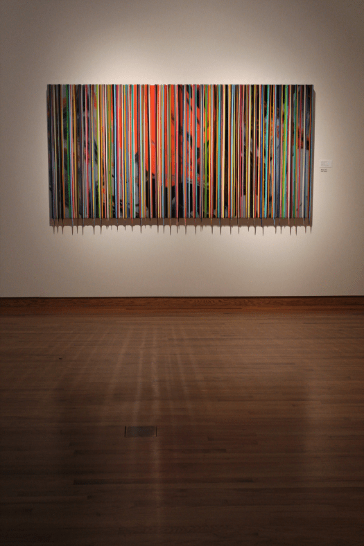 A drip painting by Valverde mixes an abstracted background of paint pours with fine-lined drips extending vertically down the composition, of varying colors and thicknesses.