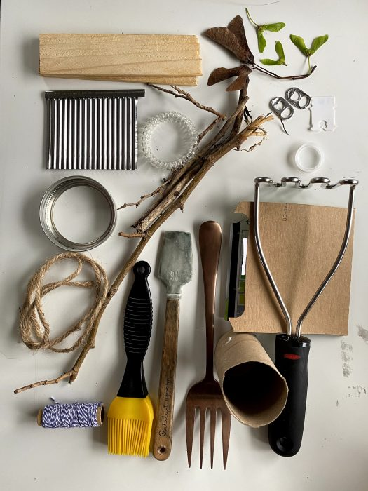 An assemblage of tools for painting without a brush: fork, sticks, twine, hairband, bottle cap, can lid, sandpaper, scraper, palette knife, and more!