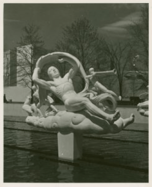 """A black and white photo of one of Manship's sculptures. """"Morning"""" shows a man half rising as if from sleep, with a rooster behind him and a smaller sculpted human blowing a trumpet in front of him."""