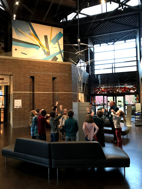Students on a field trip to FWMoA stand in the center of the atrium in the museum. They are waving their arms in an attempt to make a kinetic sculpture move, as their docent explains that the sculpture uses wind, not gears, to move.