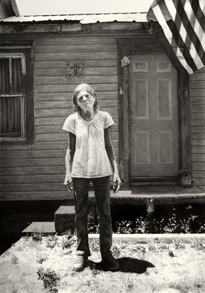 A woman stands in front a motel door, an American flag flying in the breeze off of the composition. She stands in jeans and a white t-shirt, looking directly at the viewer with her arms at her side. The growing patch of weeds at her feet and clapboard structure behind her gives a sense of neglect to the overall work.