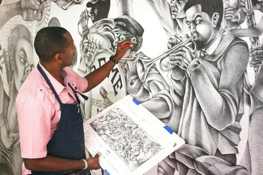 The artist working from his sketch on his mural.