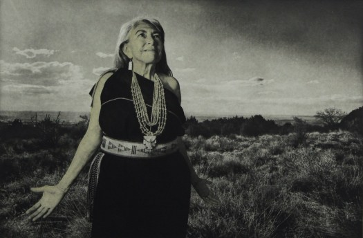 A black and white photograph of Dr Mary, a Native American woman in a black dress with Native belt standing in her Native land.