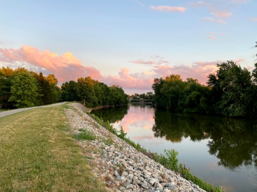 A photograph of the River Greenway in Fort Wayne, Indiana, shows the setting sun against trees and the walk trail above the river.