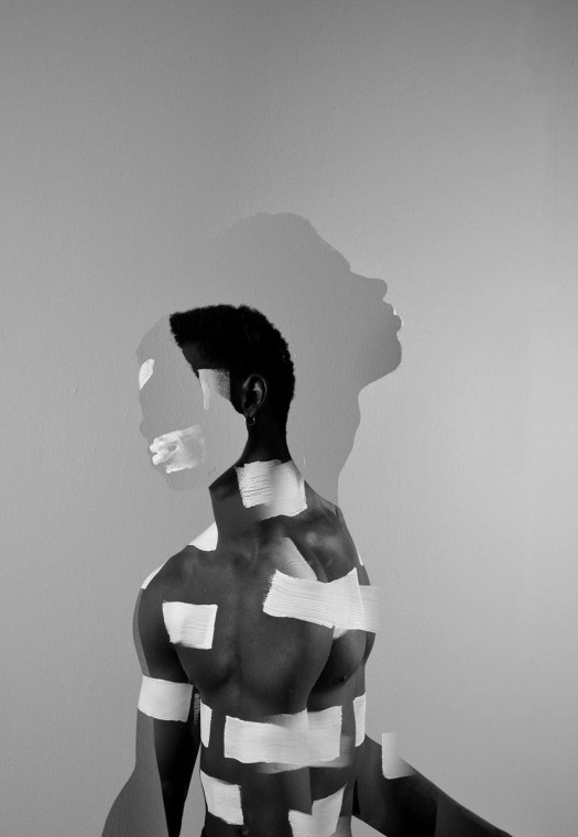 Playing with perspective, this photograph features the a Black man superimposed over another Black man. One looks the left, slouching forward while the reflection of the other looks right, head raised and throat prominent. Parts of his body are partially covered by white stripes of paint, including his mouth.