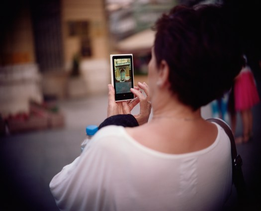 A color photograph of a woman taking a photo with her phone. Her back is to the viewer and the background is blurred out, focusing instead on the phone in lieu of the surroundings.