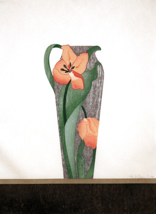 A grey pitcher with a tulip that has bloomed, and one that has not, sits atop a wooden table against a soft white background.