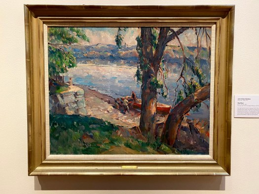 Three men struggle to heave a burden from their boat that is ashore. Behind them, mountains and trees meet the blue and purple river. In front, a grassy knoll dotted with stones and trees.