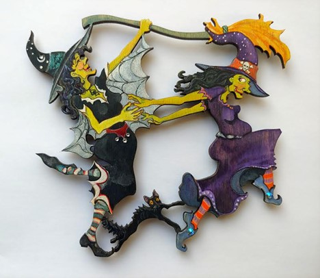 Her finished ornament shows two witches, one in black and one in purple, holding hands. Their legs are raised in a dance, and one holds a broom above the others head. In between this a black cat.