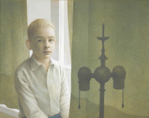 A boy sits in a window encasement, directly in front of him is a lamp. He looks at the viewer, a timid expression on his face.