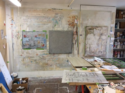 A photo showing Bob Cross's studio: unfinished works hang on the walls and paints and drawings are strewed across a large table.