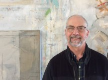 Another photograph of the artist in his studio, standing proudly next to a finished painting.