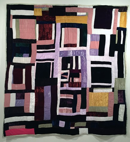 A quilt of velvet strips, mostly of purple, pink, black, and green. In the bottom left corner is one bright pink square of cotton.