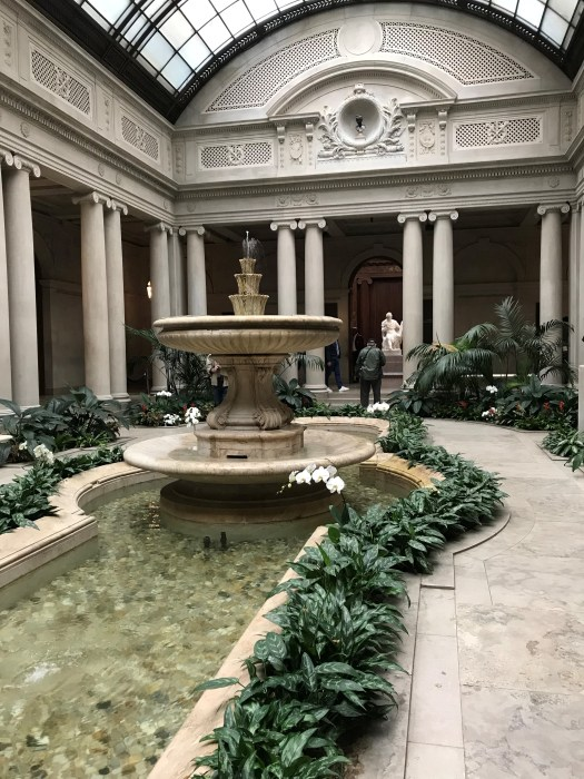 The lobby of the Frick Collection includes a fountain, plants, and a reflective pool.