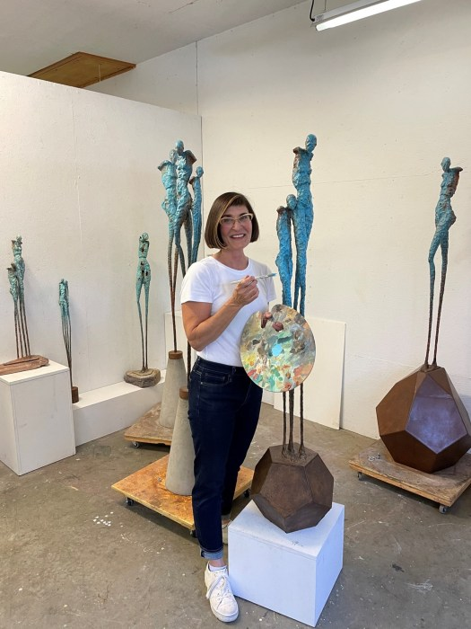 The artist in her studio, paint palette and paintbrush in hand, working on layering colored paint to a resin sculpture.