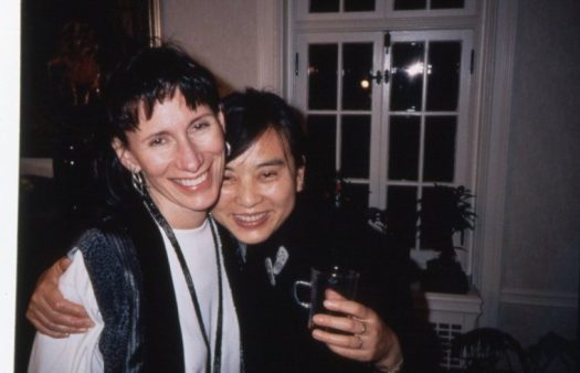 A photograph of the artist, smiling and holding a mug, one arm around the shoulder of a former FWMoA Director.