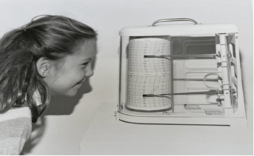 A young girl looks at a hygrothermograph, the machines found in museums and galleries that track fluctuation in temperature and humidity.