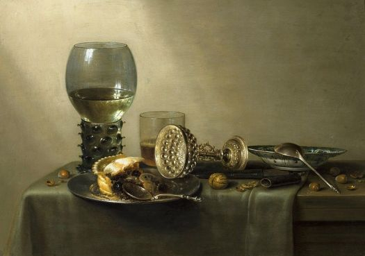 A sparse table, covered by a silk cloth, holds a half eaten slice of pie, multiple goblets, one overturned, and a soup tureen.