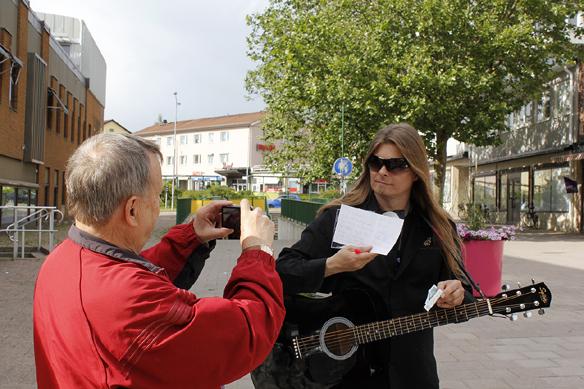 """Peter signerar sin nya skiva: """"Fy fan vad jag hatar soc"""", och skriver samtidigt ett personligt brev till gitarrläraren Lasse. Texten lyder i korthet: """"Att finna kärleken är det bästa som finns i livet - kärleken till musiken är det näst bästa - och den kärleken är ofantligt stor. Du vet vad jag pratar om Lasse eftersom du själv är musiker!"""" -  Han blev jätte glad av att få detta brev och skivan, berättar Peter. han tog i hand och tog även en bild för att dokumentera det speciella tillfället. Foto: Hasse Sukis"""