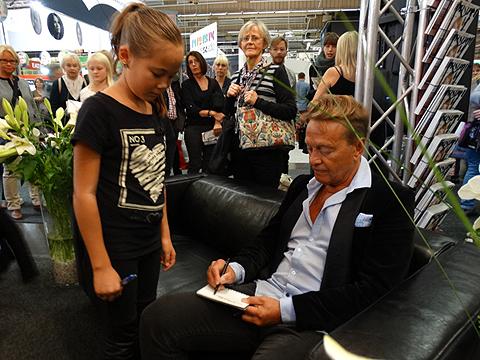 Björn Ranelid är en älskad människa av folket - men ofta föraktat av vissa inom kultur Sverige. Här skriver han autograf till en beundrande flicka under bokmässan 2014. Foto: Peter Ahlborg
