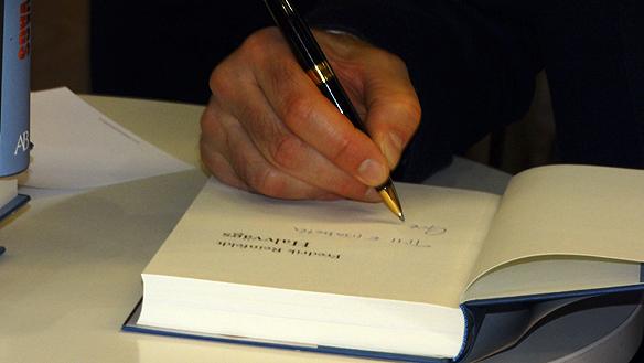 Fredrik Reinfeldt skriver så pennan glöder under besöket på bokmässan 2015. Foto: Peter Ahlborg