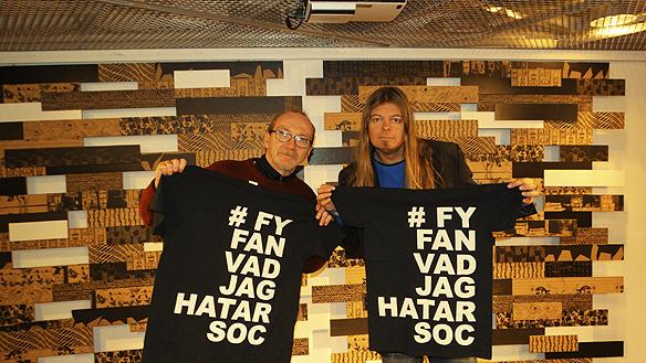 """Min gode barndomsvän Peter Lindahl får ett par T-shirt av mig Peter Ahlborg med texten """"Fy fan vad jag hatar soc"""" - när vi sammanstrålar och pratar på Kulturhuset i Stockholm. """"Målet är att minst en procent av Sveriges befolkning ska äga en av dessa T-shirt"""", säger Peter Ahlborg. Foto: Hasse Sukis"""
