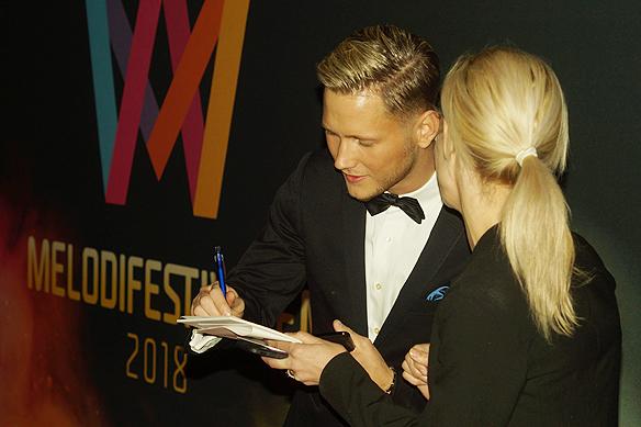 Viktor Frisk skriver en autograf när han anländer Blå hallen och ska äta en middag i Stadshuset i samband som Melodifestivalen har välkomstfest den 7 mars 2018. Foto: Peter Ahlborg