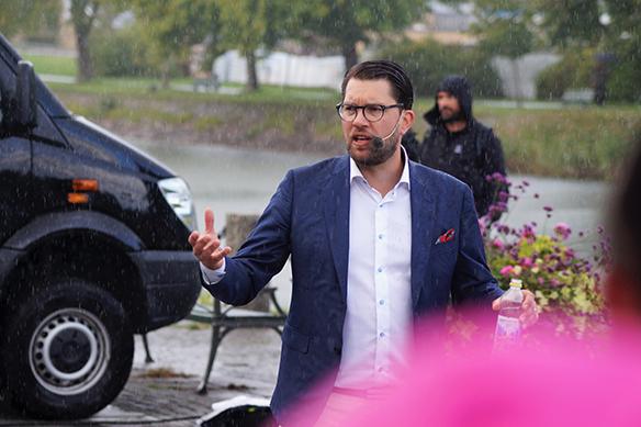 """""""Om man kommer till Sverige och ställer en massa krav på att vi ska anpassa oss till hur det var i det gamla hemlandet - ställer krav på att man ska få lov att bygga gigantiska moské-komplex - och kräver att svenska domstolar ska ta hänsyn till sharialagstiftning. Ställer man den typen av krav då ska man inte bo i Sverige. Då ska man bo i ett annat land"""", säger Jimmie Åkesson bland annat, i ett regnigt torgmöte i Vänersborg den 25 augusti 2018 inför storpublik. Foto: Peter Ahlborg"""