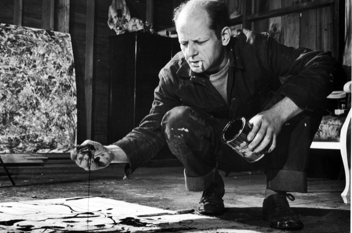 Jackson Pollock, with a cigarette in his mouth, squats next to a canvas as he drips paint on it