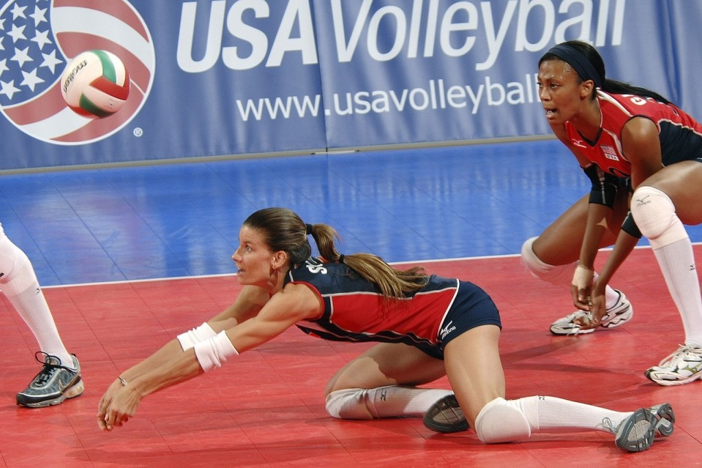 A diving volleyball player bumps a ball during competition