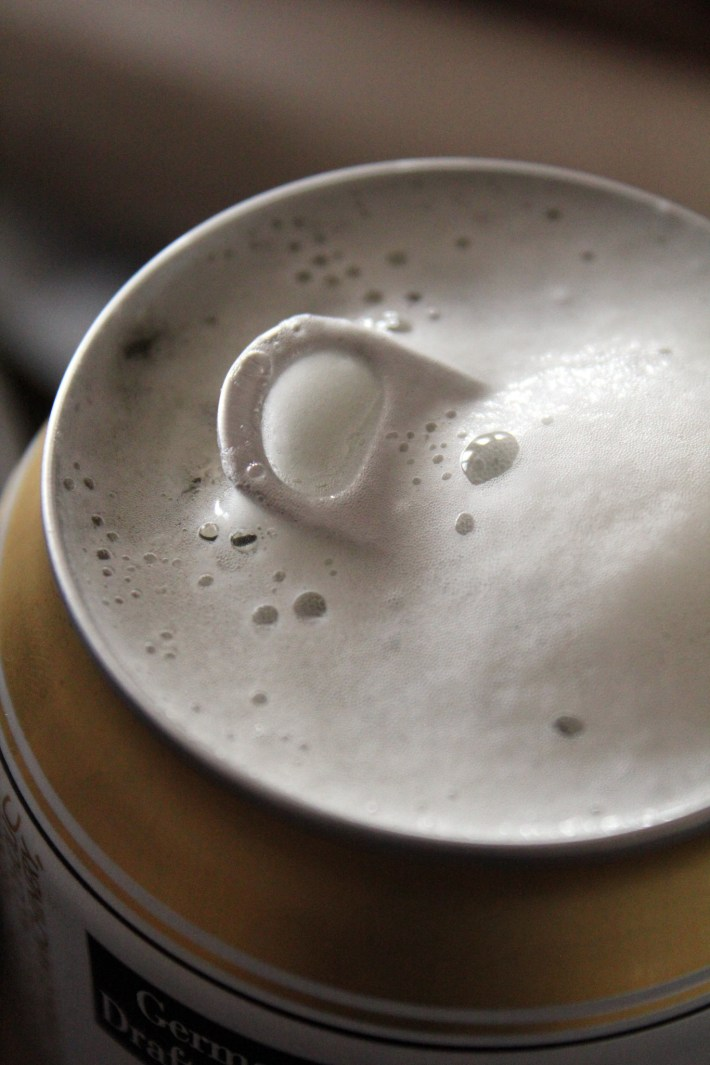 A partially opened beer can, covered in foam.