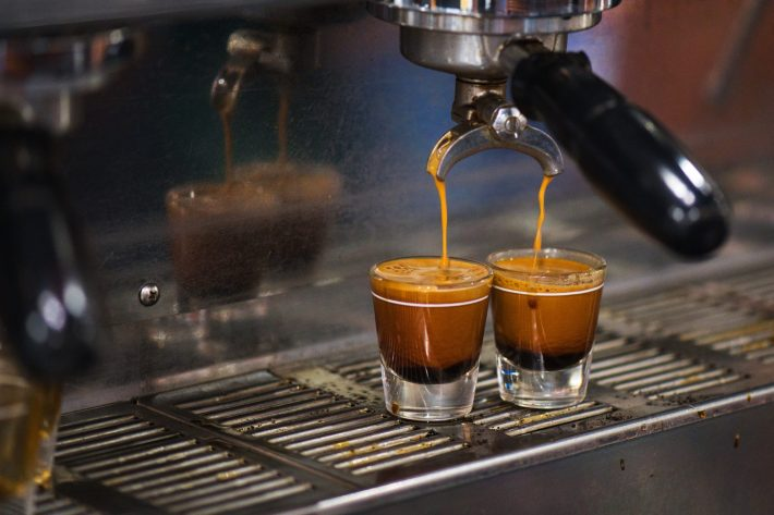 Two espresso glasses on an industrial espresso maker.