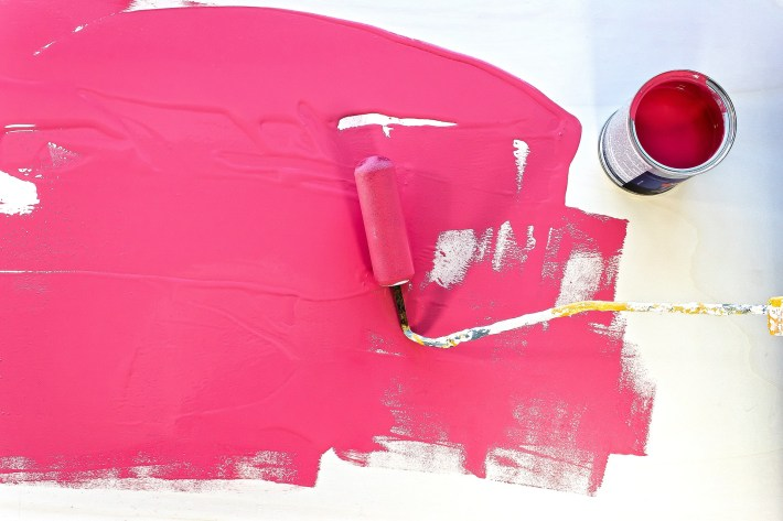 Pink paint dripping after spreading with a roller.