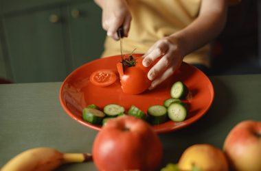 A boy slices a tomato.