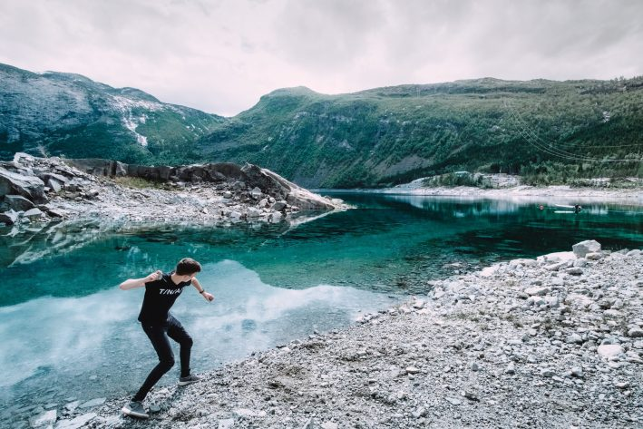A young man skips stones on a blue-green lake in Norway, surrounded by mountains.