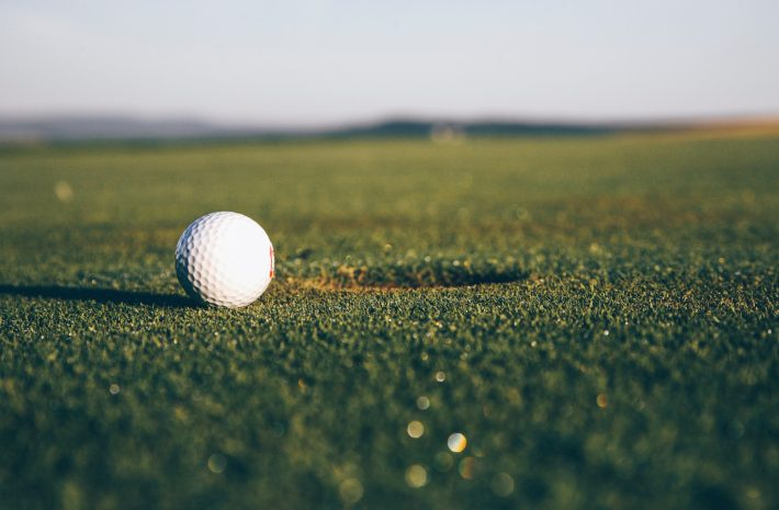 A white golf ball sitting next to a hole.