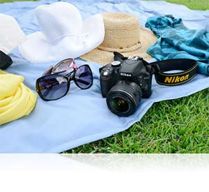 Photo of the Nikon D3300 and hats and sunglasses on a blanket on the grass showing lightweight design