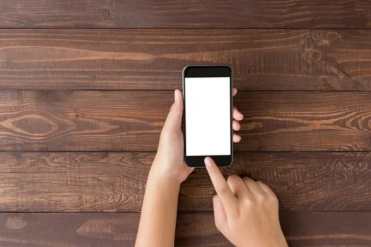 A hand holds a smartphone with a blank screen.