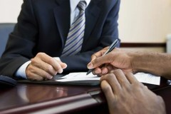 Person signing mortgage paperwork.