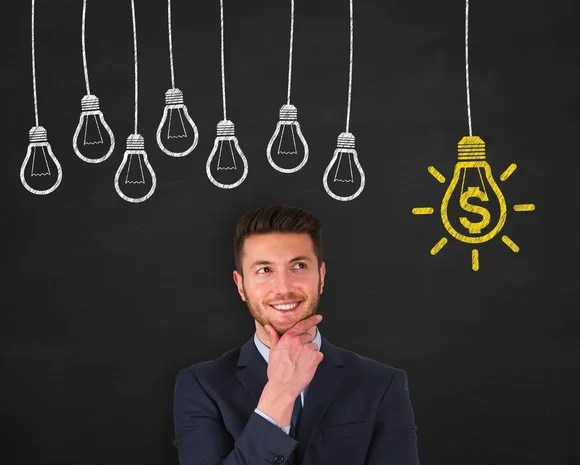 A man, standing under an illustration of a cluster of unlit light bulbs, smiles at a bulb illuminating a dollar sign.